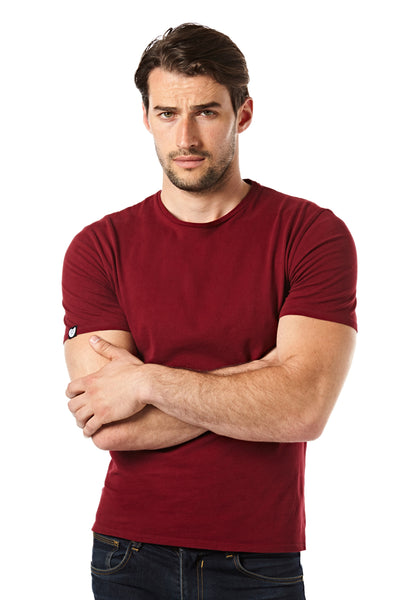 The bordeaux version of the Morph T-shirt. The model is wearing size Achilles. He is showing the snugly fitting sleeves, iconic crew neck and the small label on the right sleeve that shows his size symbol, a shield