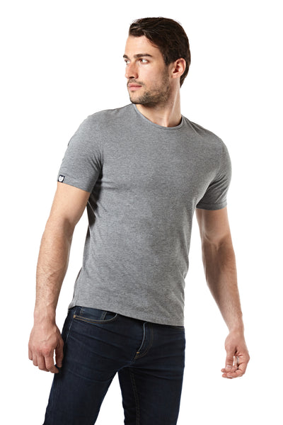 the model is wearing the grey melange Morph T-shirt in size Achilles. The way he is standing is showing the small label depicting the symbol of his size, a shield, on the right arm, the crew neck collar and the spacious fit in the chest. The T-shirt length comes exactly down to the seams of his jeans pockets.