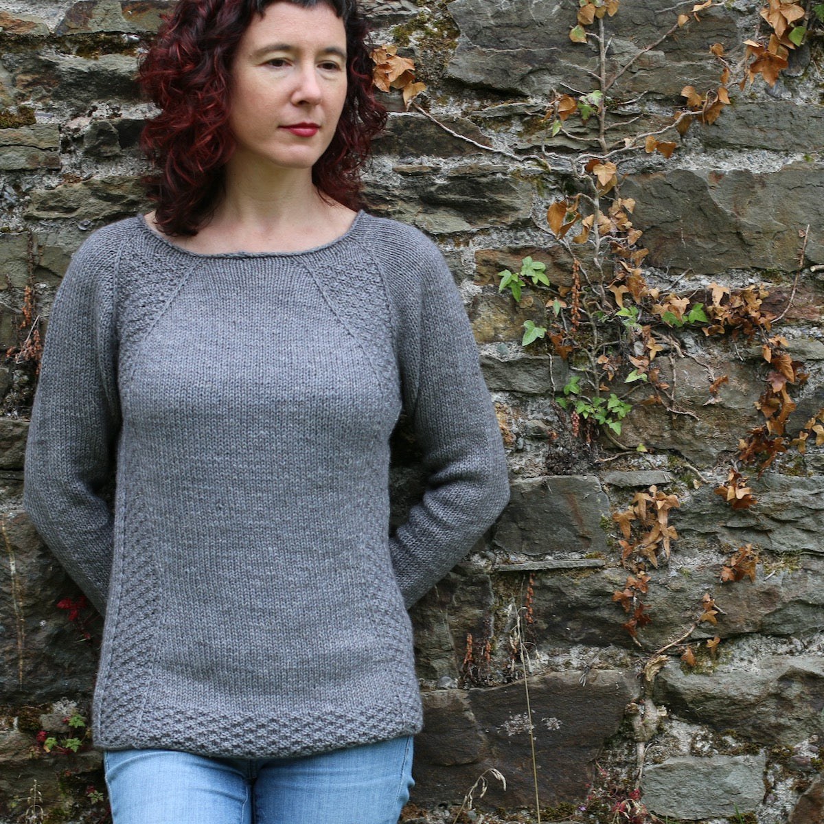 image of woman standing against a stone wall wearing a grey knitted sweater and looking down