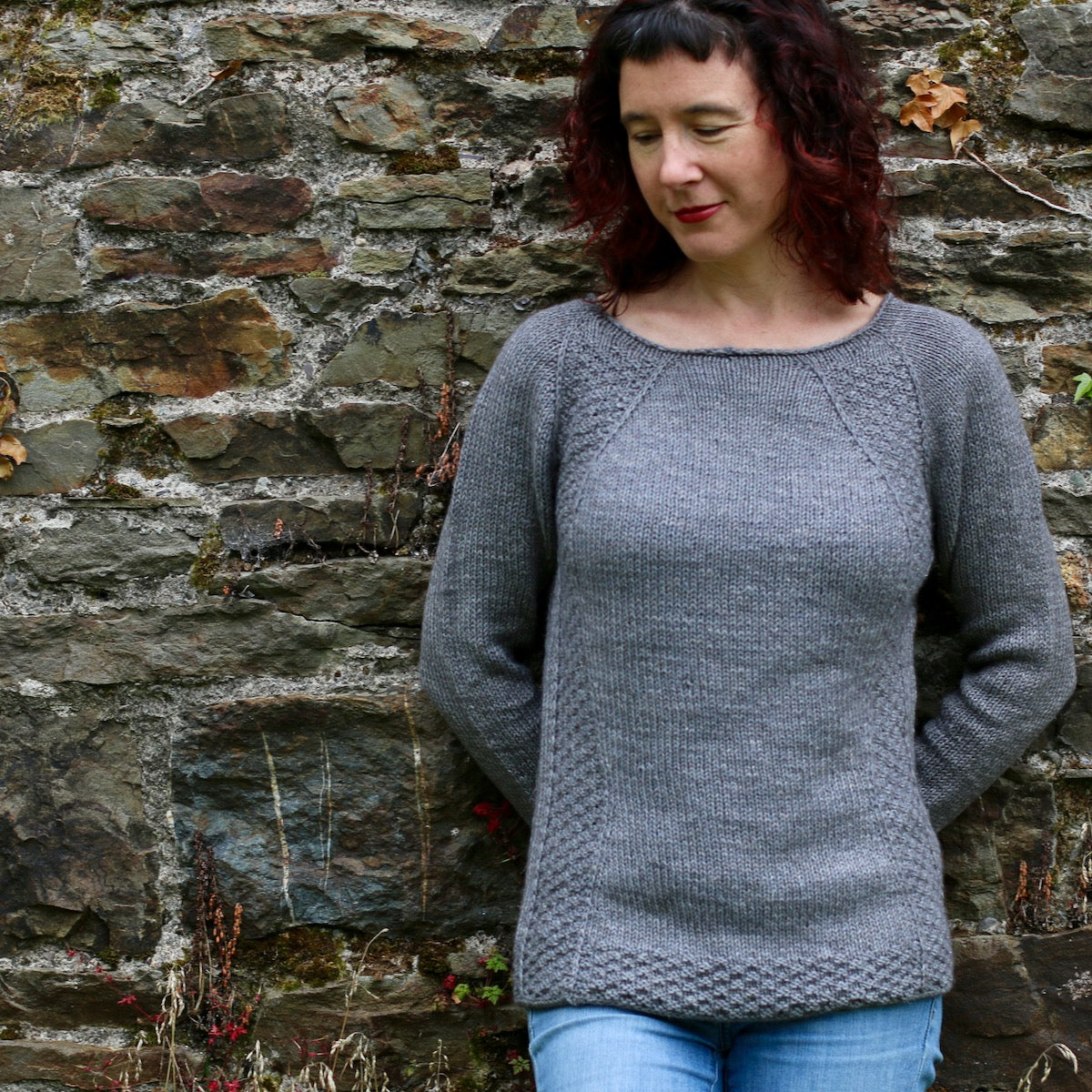 image of woman wearing a grey sweater against a stone wall looking down