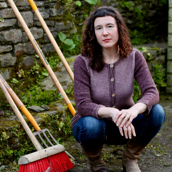 woman crouching in front of garden tools with hands clasped in front wearing a pink and purple cardigan