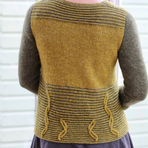 back of woman wearing laminarus cardigan in two shades of green with cables at the bottom of the body,