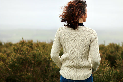 back of woman standing on hill wearing a cream cabled cardigan