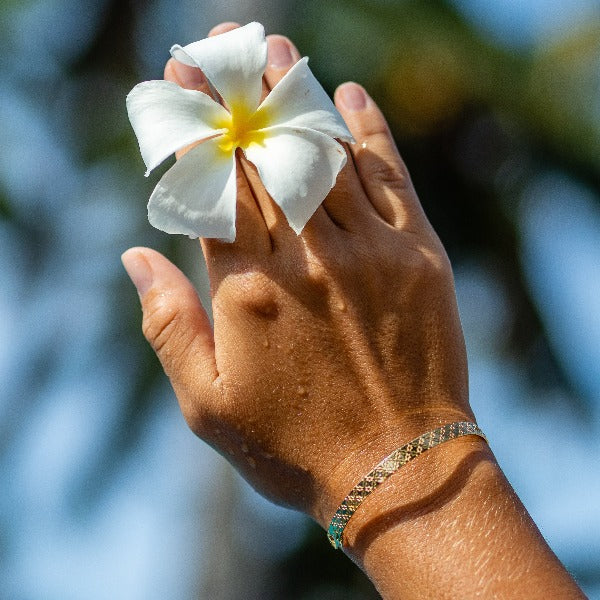 VANDAYA Floral Gold Cuff, Bali Bracelet. Gold bangle gold plated with 18 carat gold. This tropically inspired bracelet in picture with a beautiful tropical flower.