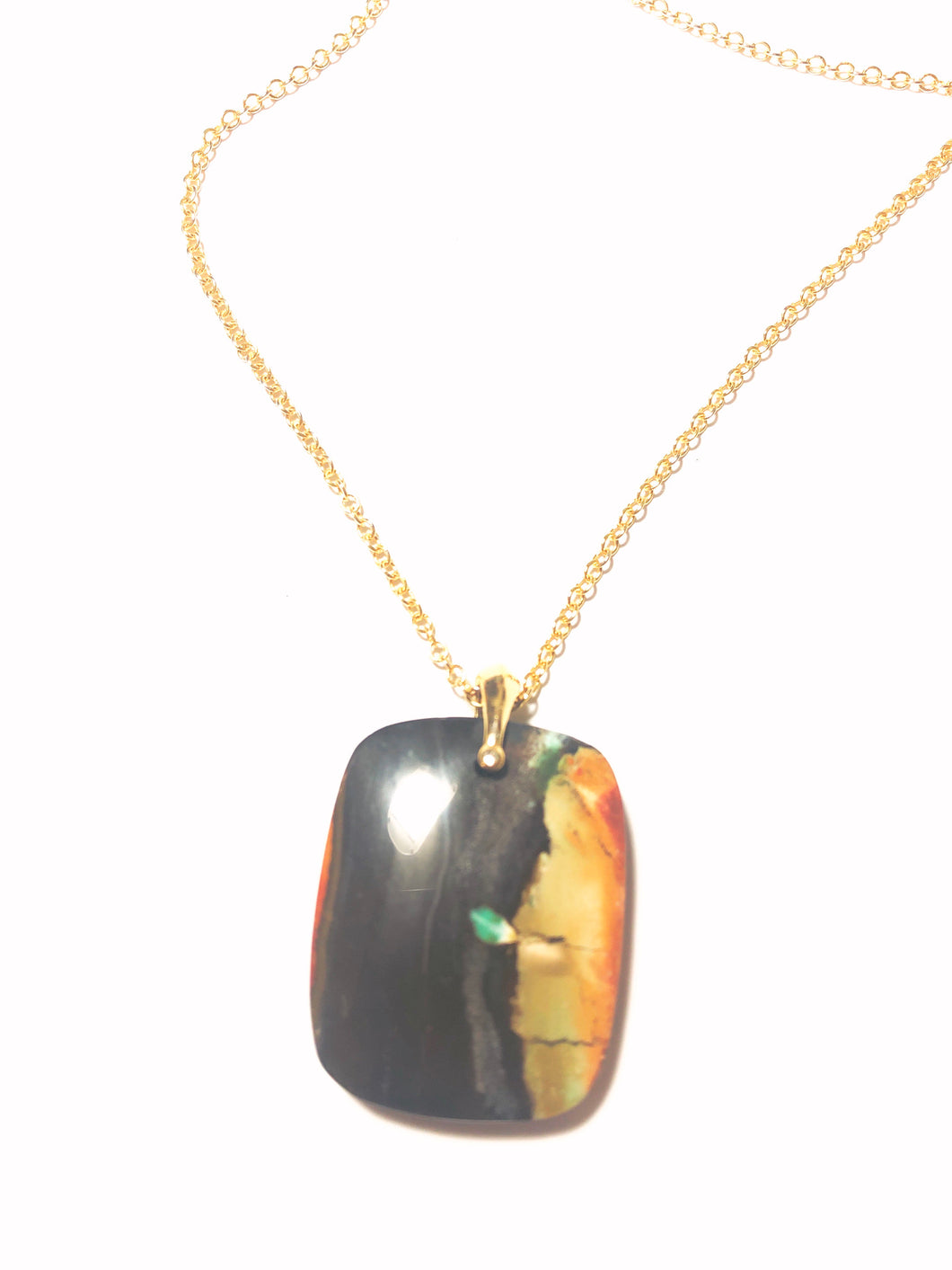 Pedant in dark color and beige, yellow and red of  opalized wood