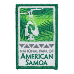Rectangular green and white patch shows fruit bat/flying fox and rainforest logo of the National Park of American Samoa and park name in green on a white background.