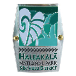 Rectangular green, silver and white hiking medallion shows the taro plant and waterfalls of Haleakalā National Historical Park on Maui.