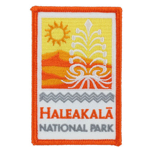 Rectangular gold, orange and white patch shows the rising sun and Haleakalā silversword over the park name: Haleakalā National Park, embroidered in orange on a white field under a kapa pattern border design.