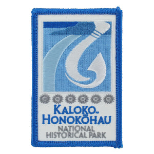 Rectangular blue and white patch shows fishhook and fishpond logo of Kaloko-Honokōhau National Historical Park on Hawaiʻi Island, as well as park name in blue on a white field.