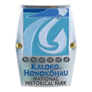 Rectangular blue and white hiking medallion shows fishhook and fishpond logo of Kaloko-Honokōhau National Historical Park on Hawaiʻi Island.