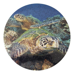 Round puzzle shows photograph of two Hawaiian green sea turtles resting on a coral reef in Hawaiʻi.