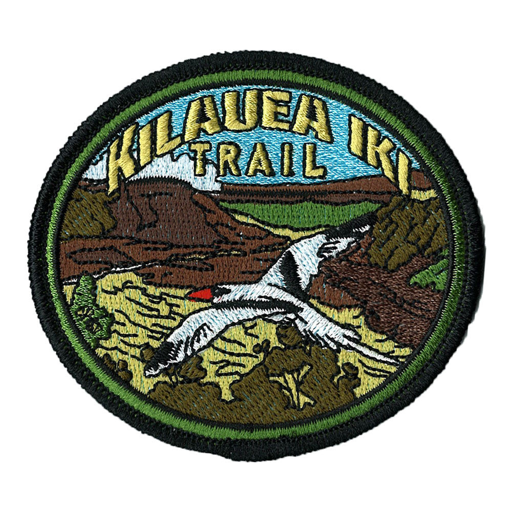 "Oval patch has the name ""Kīlauea Iki Trail"" embroidered in gold over a yellow and brown scene of the crater, with a black and white red-tailed tropicbird soaring in the foreground."
