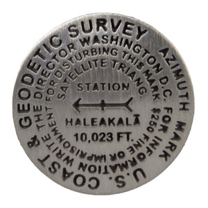 Circular metal geodesic survey marker shows height of Haleakalā national park along with other geographic data.