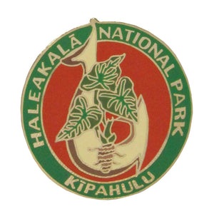 This green and red pin represents the Kīpahulu District of Haleakalā National Park, rich in Polynesian culture. The foreground of this round pin shows a fish hook, once made from shell, hardwood or bone. The taro plant, a Hawaiian staple food, is also represented. The park name, Haleakalā National Park, runs around the top 3/4 of the pin.
