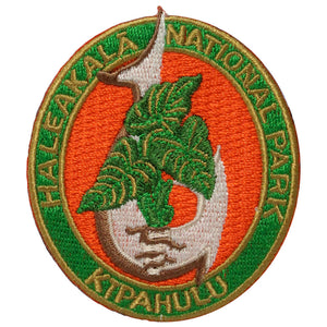 "Oval patch has the name Haleakalā National park embroidered in green around a red field showing a taro/kalo plant growing through a traditional Hawaiian fish hook. The word ""Kīpahulu"" is embroidered on the bottom of the oval."