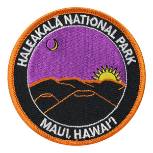 Round patch has name of Haleakalā National Park and Maui, Hawaiʻi embroidered around the edge of a scene depicting a purple sky with a rising gold sun and the sliver of a moon, over dark cinder cones rimmed in dawn light.