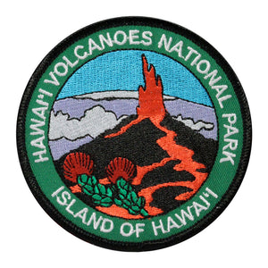 Round patch has name of Hawaiʻi Volcanoes National Park and Island of Hawaiʻi embroidered around the edge of a scene depicting a lava fountain erupting from a cinder cone, with the native Hawaiian ʻohiʻa lehua blossoms in the foreground and a snow-capped Mauna Kea under a blue sky in the background.