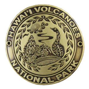 Metal medallion is 1.75 inches in diameter, gold, with engravings of a nēnē, a volcanic plume and native plants.