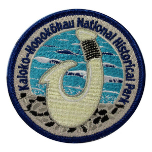 Round patch has name of Kaloko-Honokōhau National Historical Park embroidered around the edge of a scene depicting a white traditional bone fish hook against the blue and white ocean..