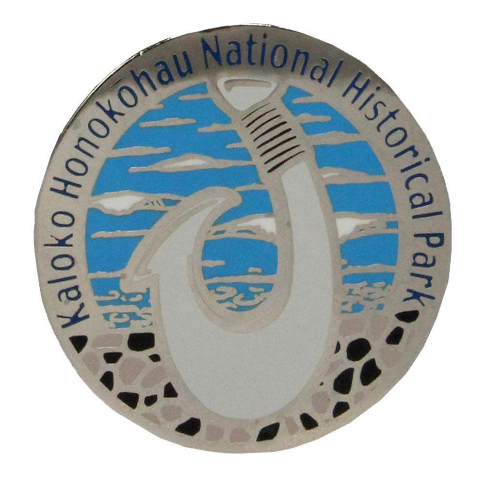 Pin shows a Hawaiian fish hook carved from bone or shell, a symbol of the advanced fishing techniques and achievement of early Hawaiian fishermen. Round enameled metal pin in blue, white and black is 1.25 x.75 inches in diameter and has the park name, Kaloko-Honokōhau National Historical Park, running around the top 3/4 edge of the pin.