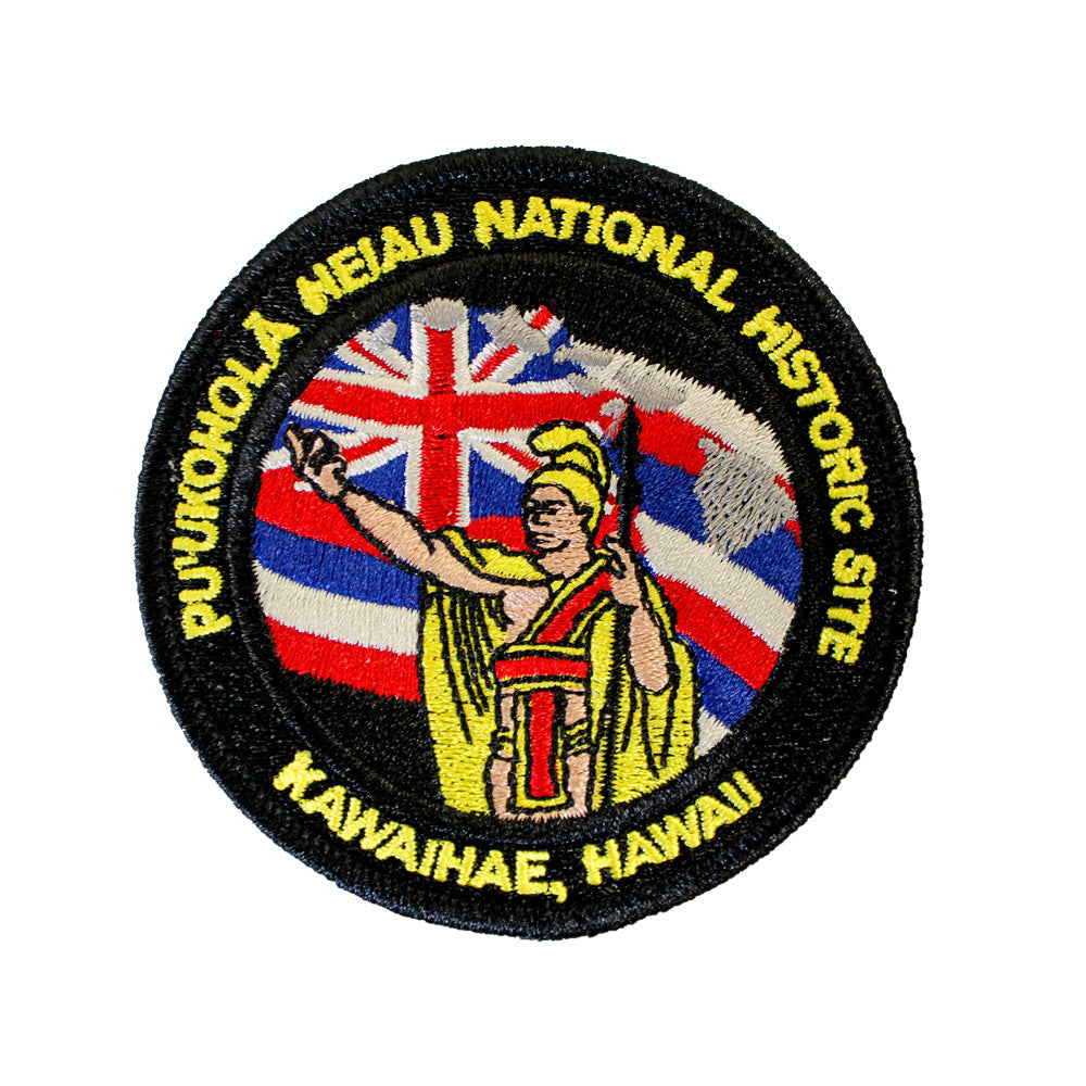 Round patch has name of Puʻukoholā Heiau National Historic Site embroidered around the edge of a scene depicting Kamehameha, Hawaii's first king, standing in yellow and gold regalia in front of the Hawaiian flag with his arm raised..
