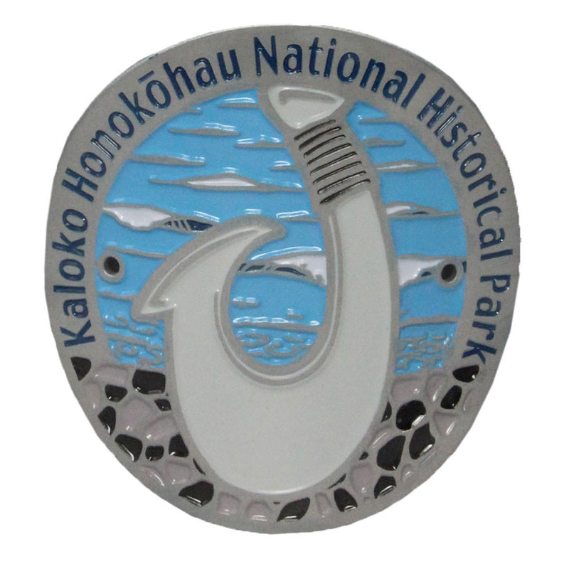 Oval pin with grey rim stating the name of the park: Kaloko-Honokōhau NHP. Pin shows a white bone traditional fish hook on a blue background representing the ocean.