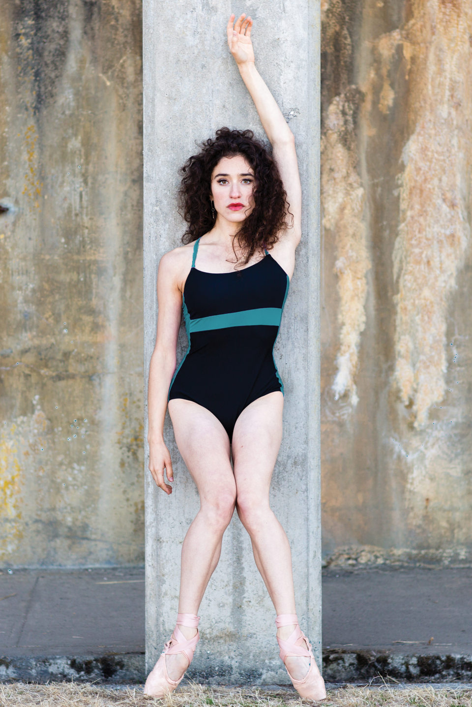 dancer on pointe wearing black leotard with green stripe strappy leotard