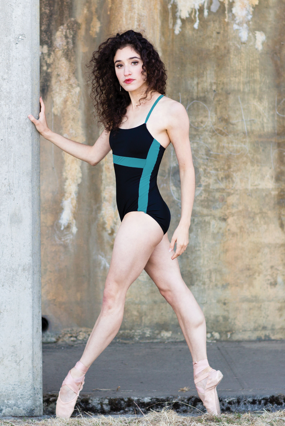 dancer on pointe wearing black leotard with green blocks and small straps
