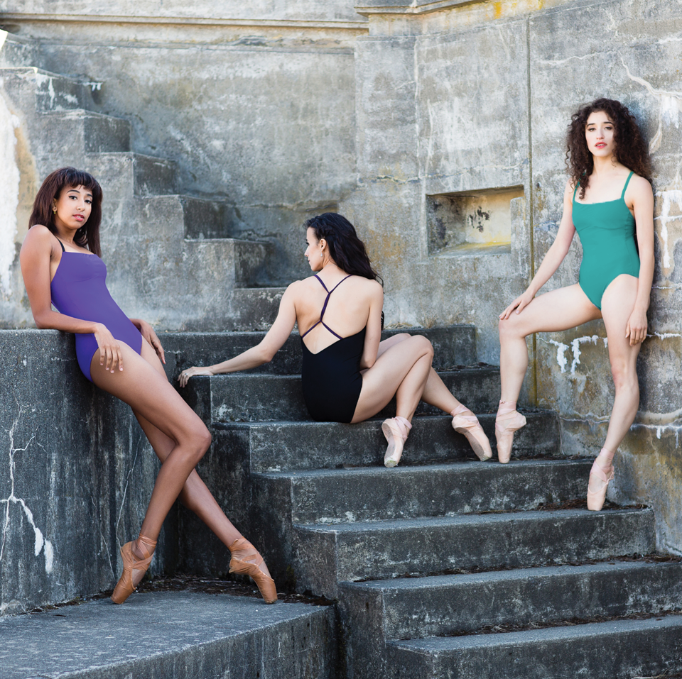 three dancers wearing solid color ballet leotards with thin straps and twisted back