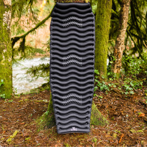 Black Wavy Sleeping Pad leaning against tree