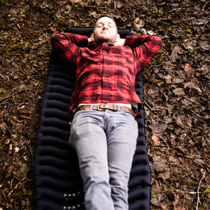Man laying on Black Wavy Sleeping Pad