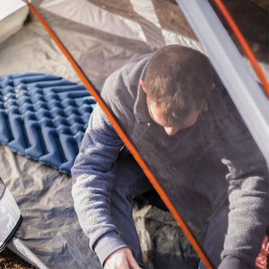 Man in tent with Blue Sleeping Pad