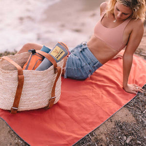 Woman sitting on Red Camping Towel