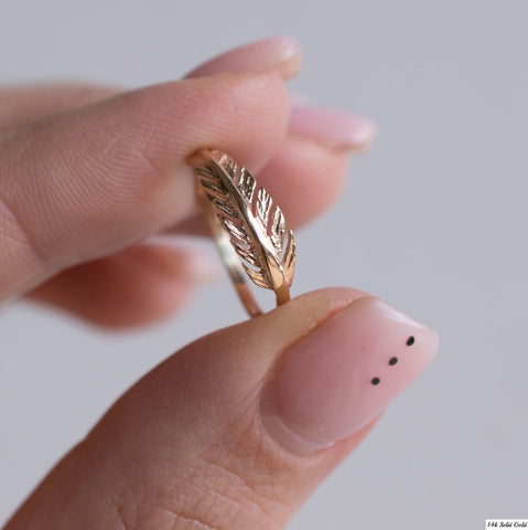 Fingers Holding a Rose Gold Feather Ring