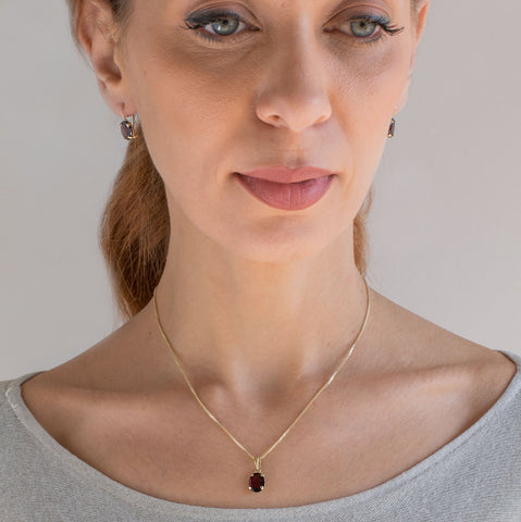 garnet oval gold earrings and necklace set on model