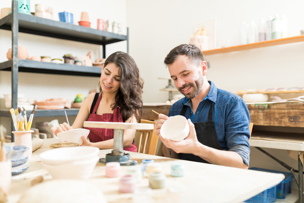two adults taking a pottery class
