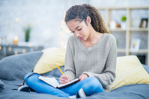 young woman journaling in bed