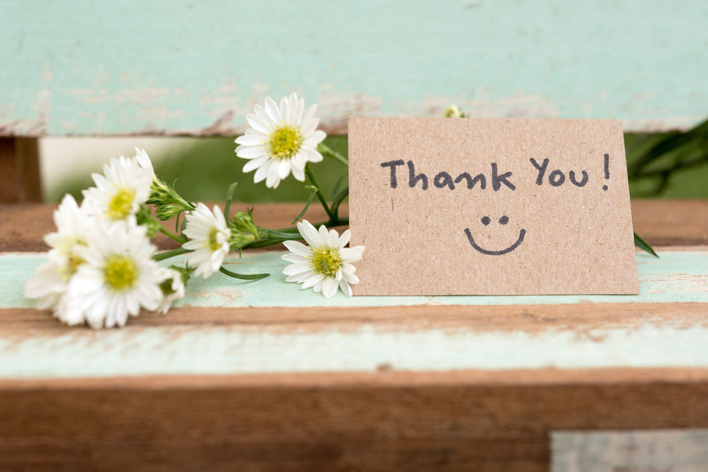 thank you card sitting in front of flowers