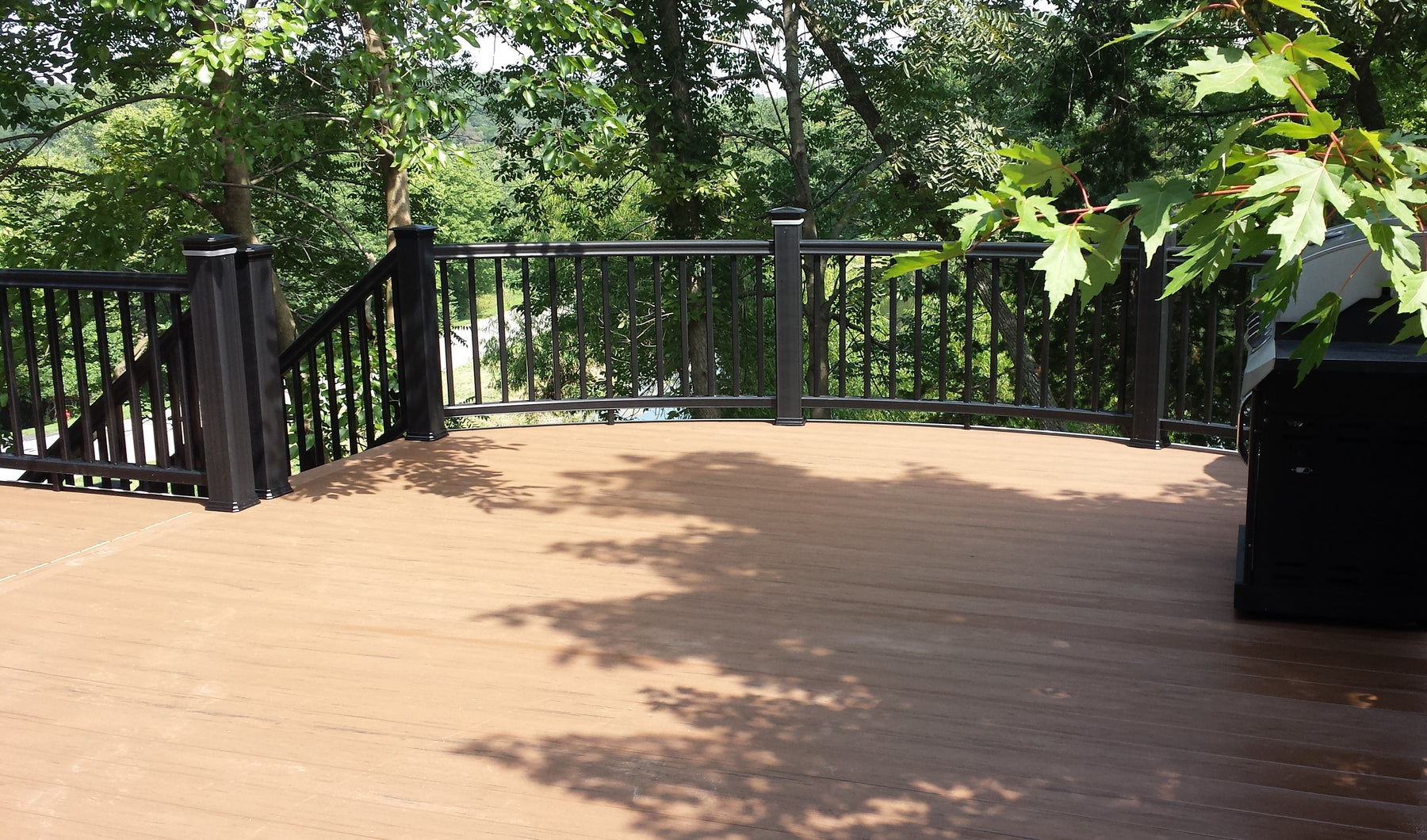Curved Front Railing, Composite Curved Rail in RadianceRail Composite Railing with TimberTech Terrain Decking a capped composite brown decking, also has lighted light rings or glow rings in the post cap, lighted by led