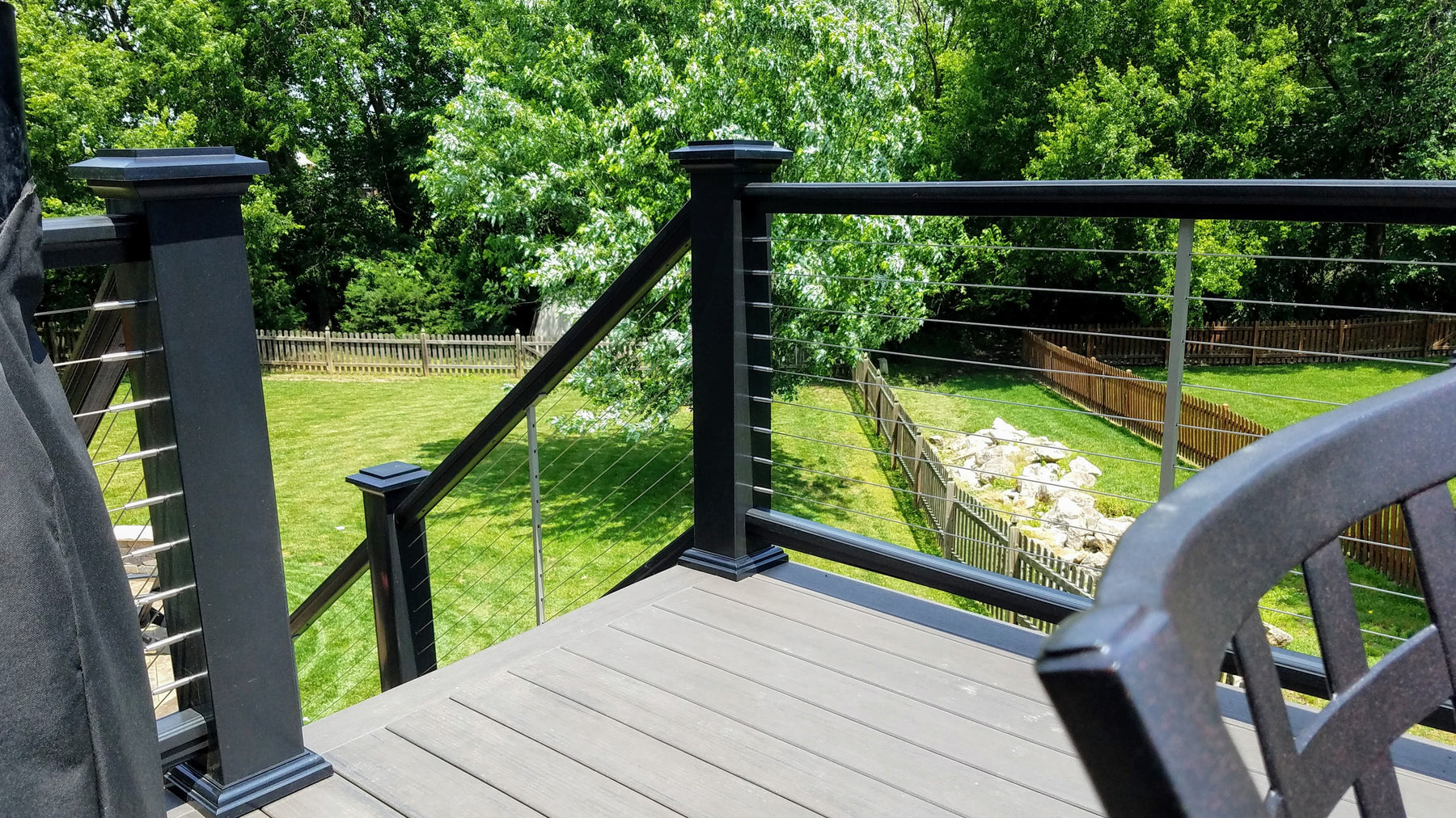 Composite Premier Rail a TimberTech Railing System with Cable infill, and Lighted Island Post Caps in Black colored railing, post sleeves, post caps, and post flairs