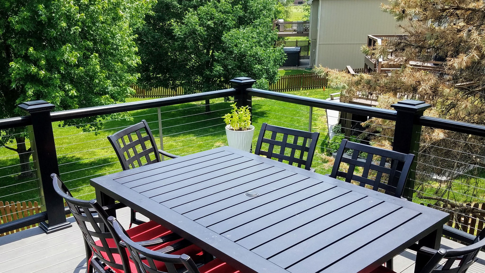 Back deck table with chairs and view of backyard though cable rail by feeney, rails by azek and decking by timbertech for a low-maintainance, easy-to-maintain wonderful space