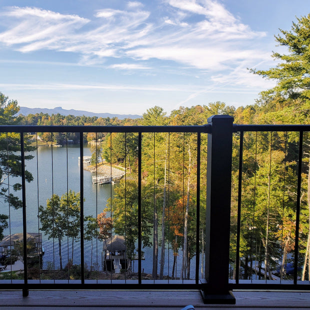 C80 VertiCable beautiful background of lake and trees, walkout deck railing vertical wired stainless steel cable rail c80 with 4in x 4in posts, bright sky and mountains in the distance. Photo Credit: Megan Wilson