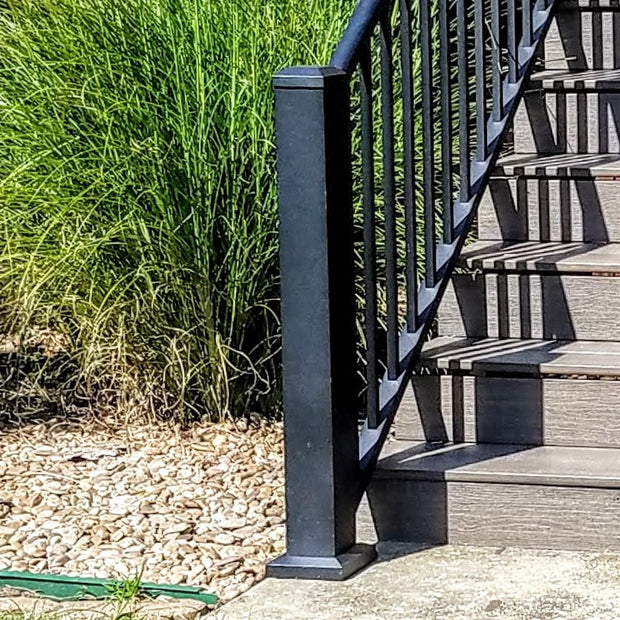 "Westbury 47"" 4x4 post for bottom of stairs infront of green bush aluminum railing in black fine texture"