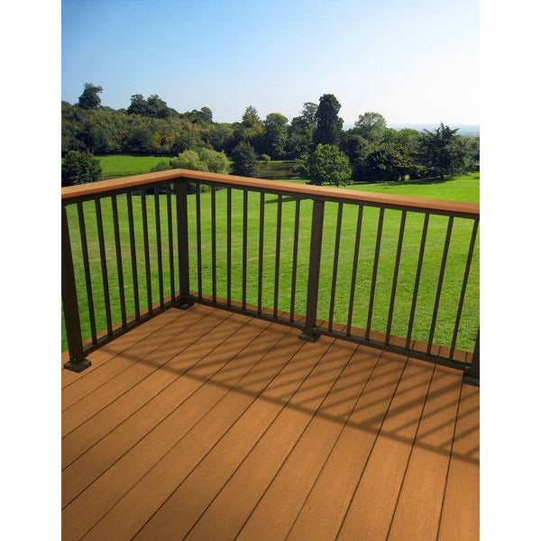 Westbury Drink rail with deck board on a cedar toned deck, aluminum westbury railing infront of an open grassy area and trees in the distance
