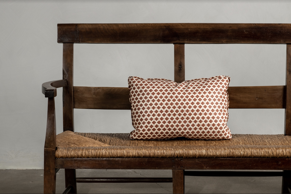 "One 18"" x 12"" Knurl Brick Nickey Kehoe Collection Pillow on a bench."