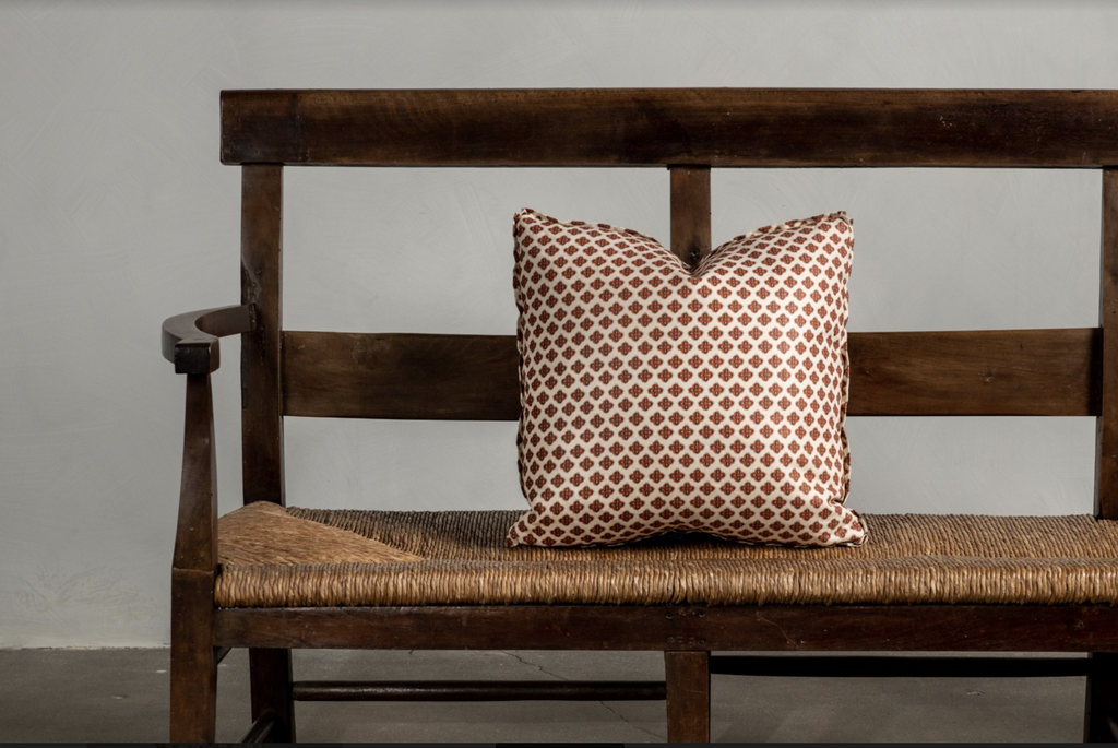 "One 16"" x 16"" Knurl Brick Nickey Kehoe Collection Pillow on a bench."