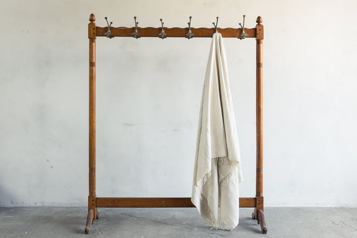 One Creative Women Cotton Throw Blanket on a rack.