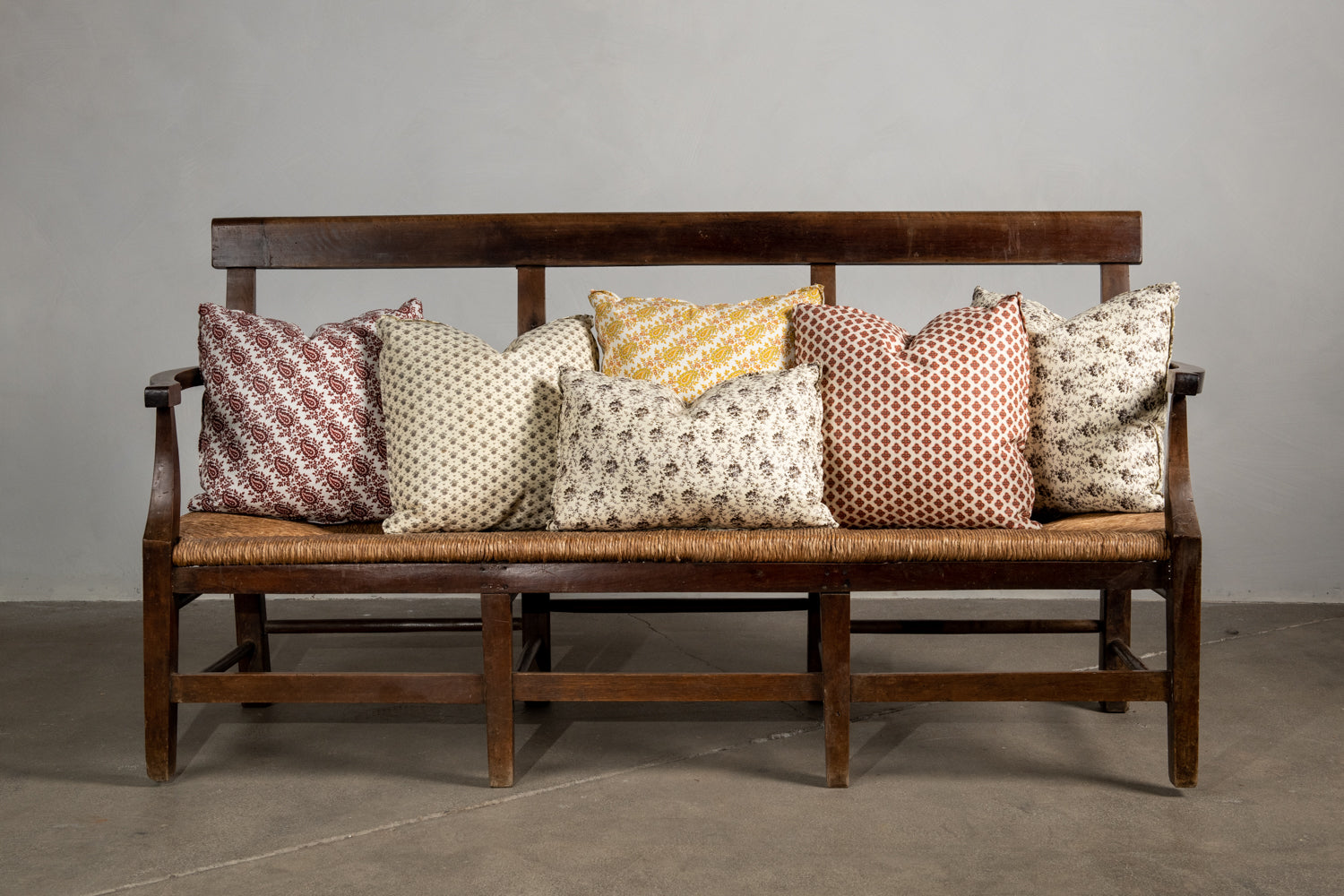Assorted Nickey Kehoe Collection Pillows on a bench.