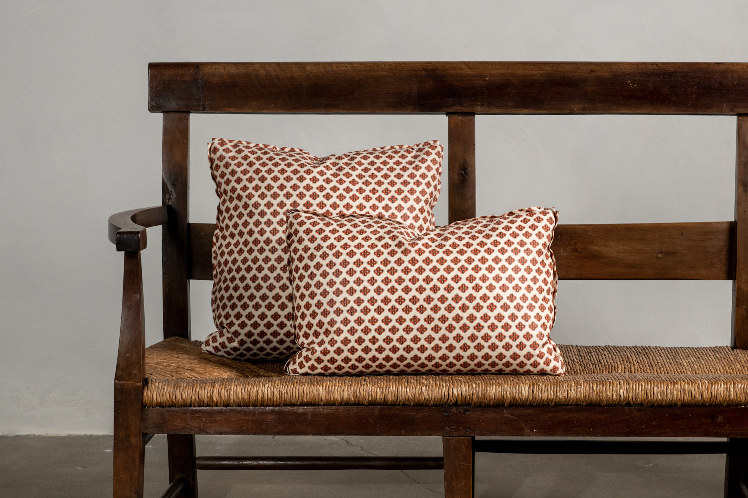 Two Nickey Kehoe Collection Knurl Brick Pillows on a bench.