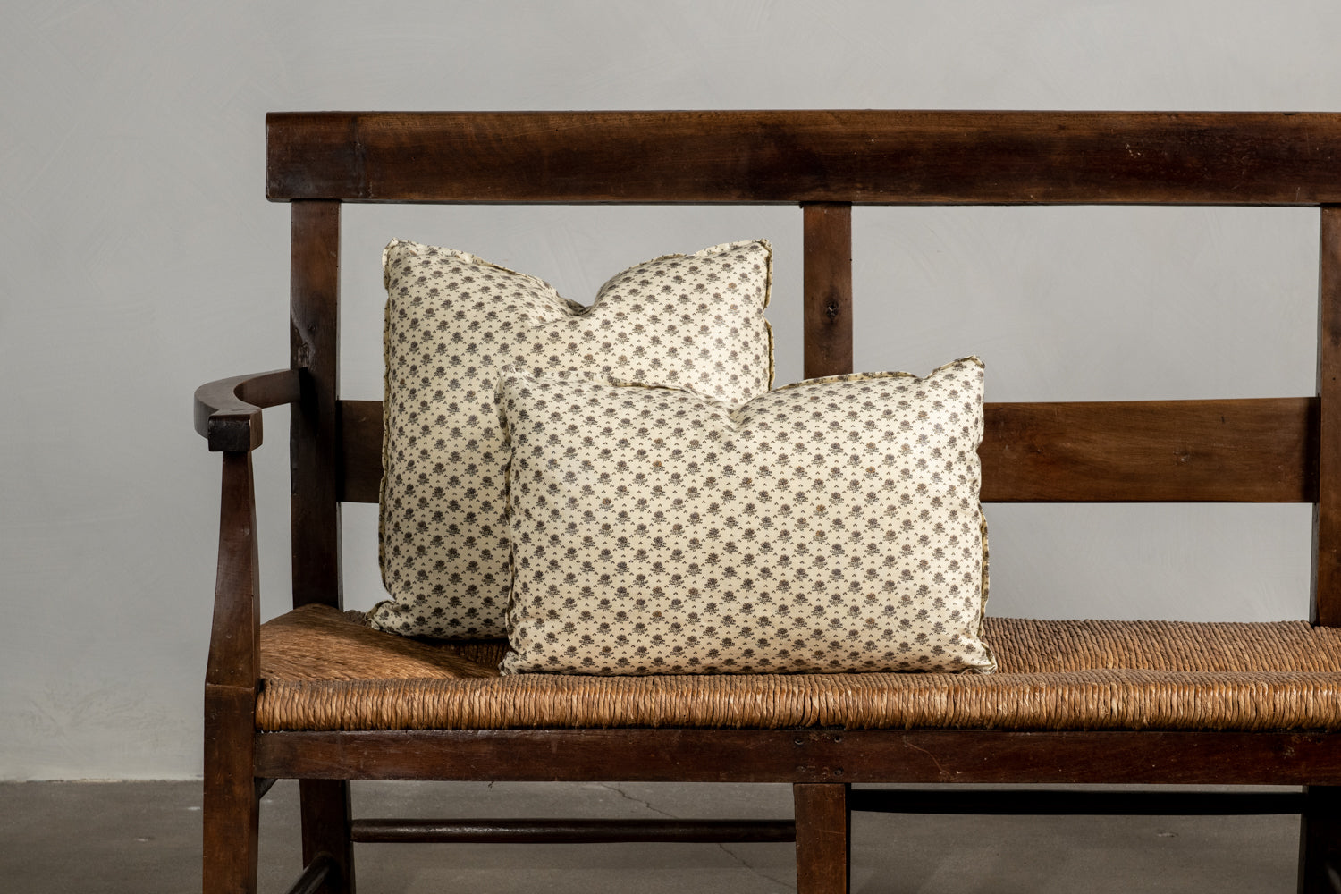 Two Littleweed Linen Nickey Kehoe Collection Pillows on a bench.